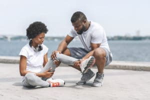 Man helps woman with injury on the sea shore | Featured image for ankle sprain symptoms.