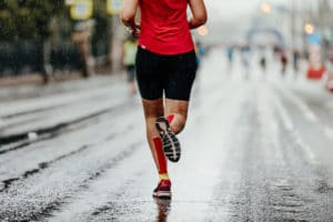 Woman running in the rain | Featured image for calf injuries article.