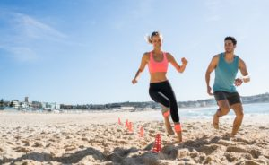 Happy young couple exercising outdoors at the beach in Australia running on the sand with obstacles e