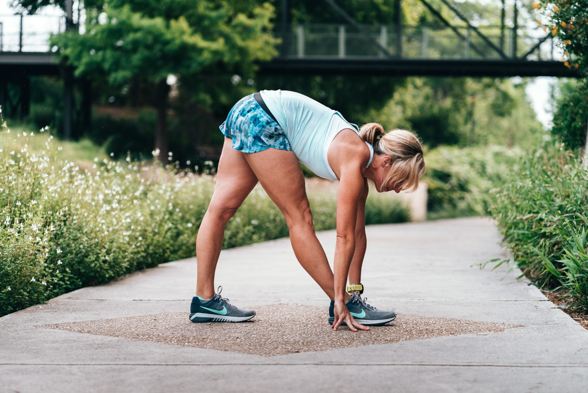 Woman wearing shorts doing stretch on path