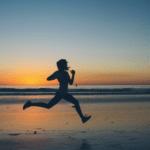 Person sprinting down a sunset beach