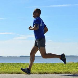 man running down grassy waterfront
