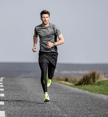 Man running down an asphalt road | Featured image for stress fractures blog.