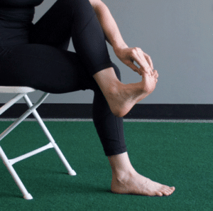 Woman massaging her toes | Featured image for managing acute soft tissue injuries with RICER and HARM blog.