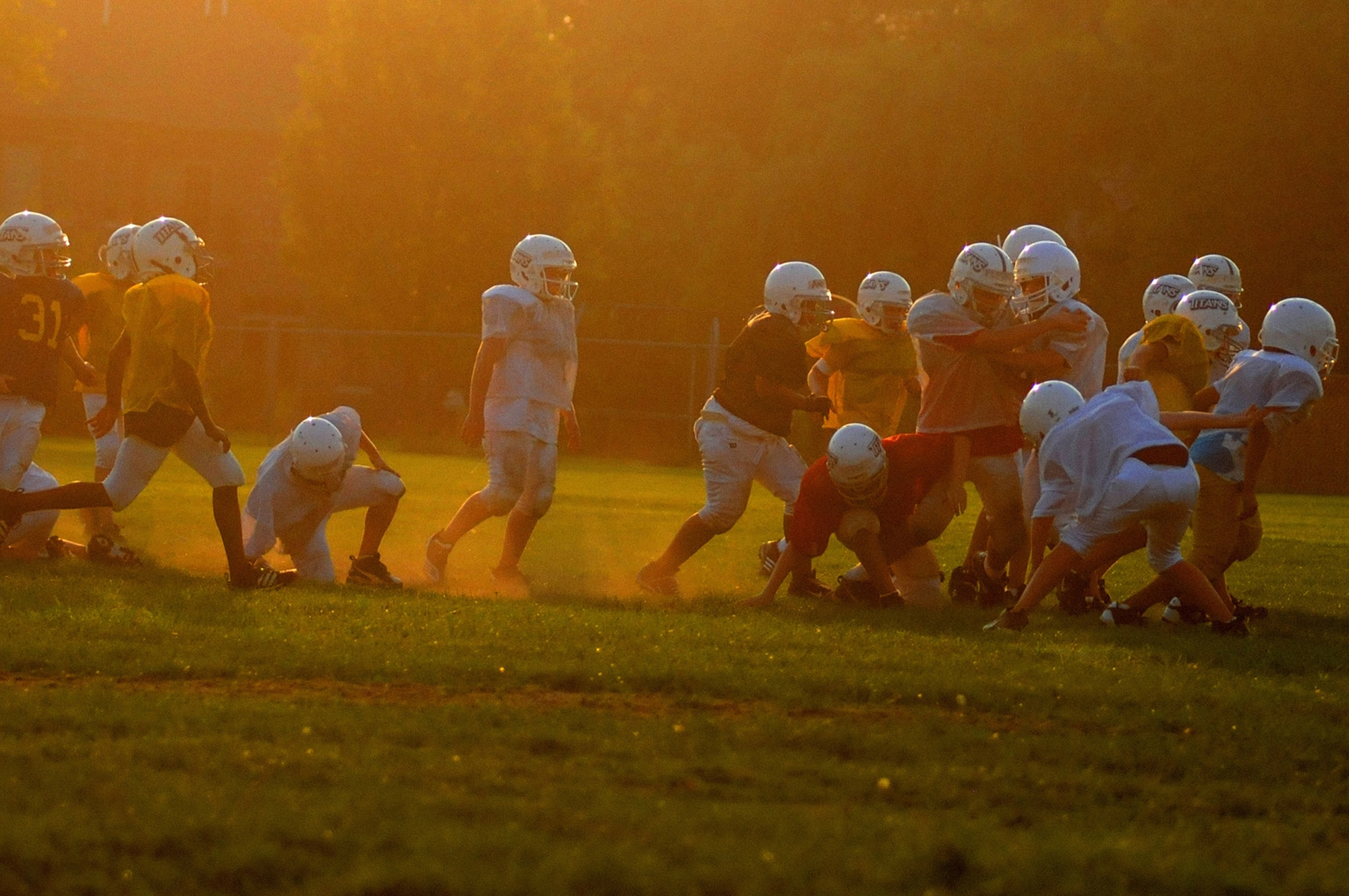 Concussion prevention blog featured image showing a team of American Football playing children wearing protective gear