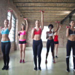 Group of woman doing exercises with pink dumbbells