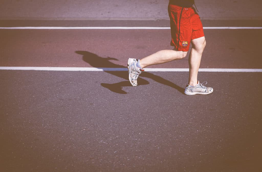 Person running on a track | Featured image for Patella Femoral Pain Syndrome Article.