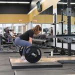 A woman performing deadlift - what is the posterior chain blog featured image.