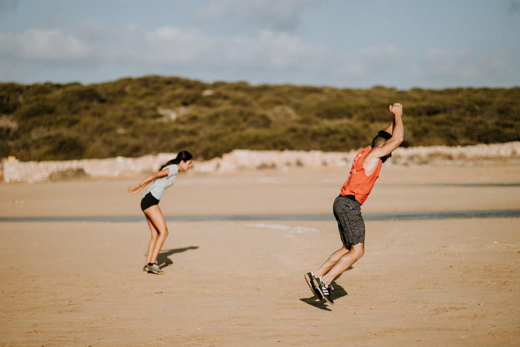 Two people exercise on the beach | Featured image for ACL Management blog.