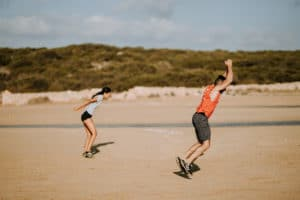 Two people exercise on the beach | Featured image for ACL Management.