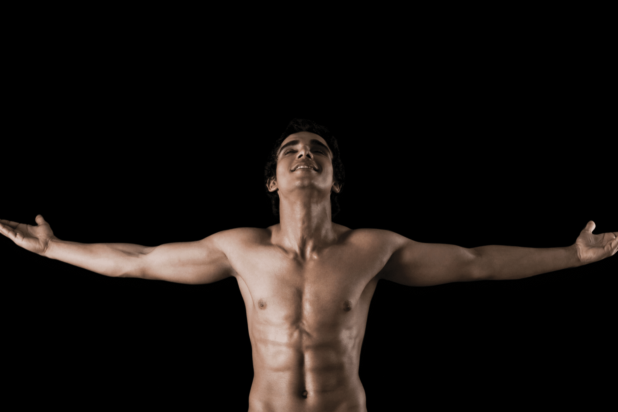 Topless person standing with arms wide open on black background.