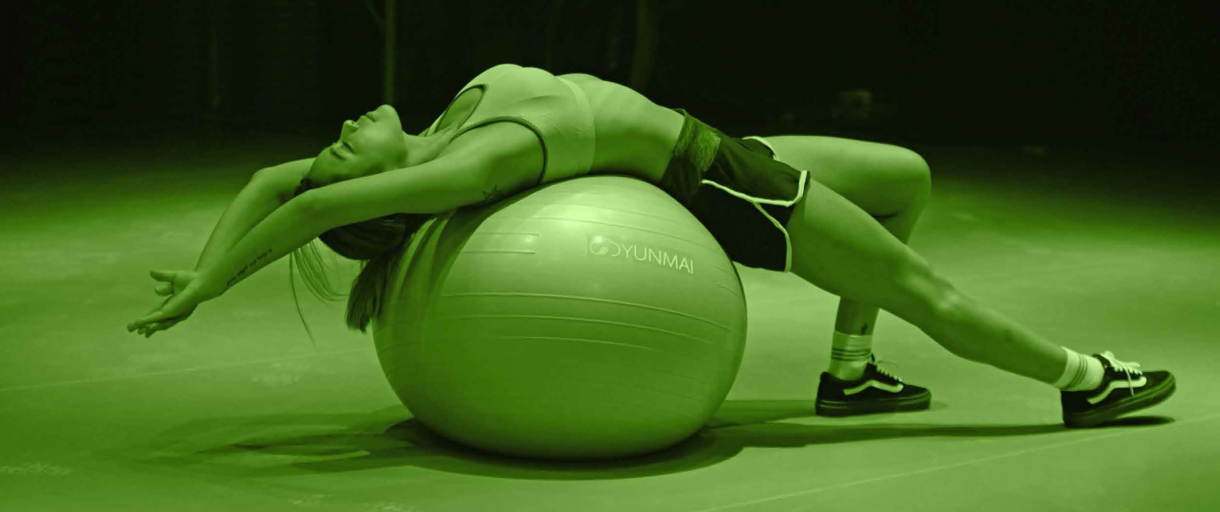 Image of woman lying back on gym ball with arms stretched out