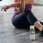 Image of women with purple tank top stretching next to Boxed water