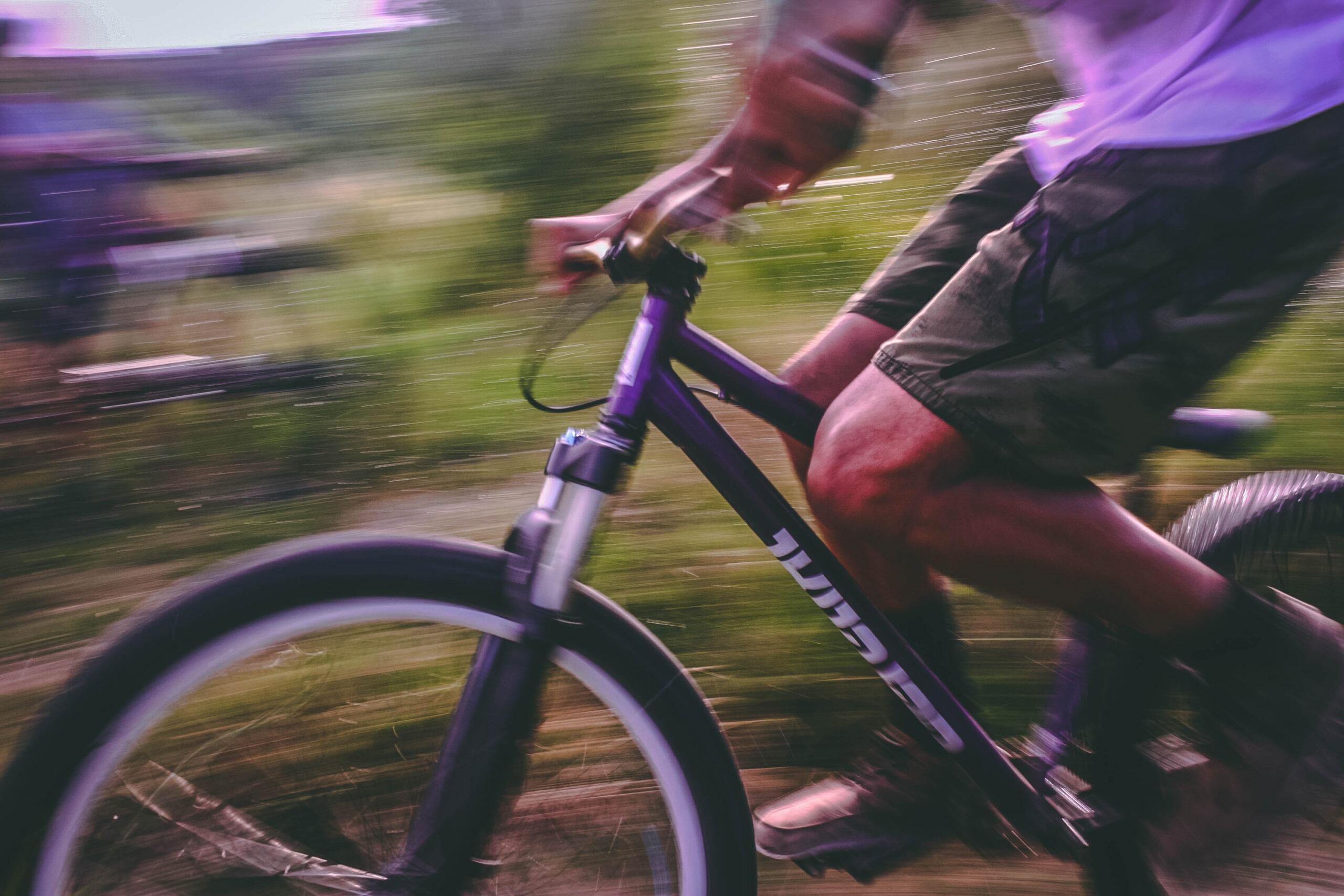 Image of guy riding bike in grassland