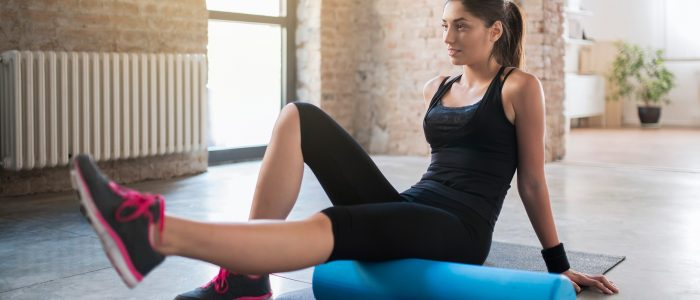 Girl wearing black tank top lying on exercise mat | Featured Image for Exercise physiologists | Landing page