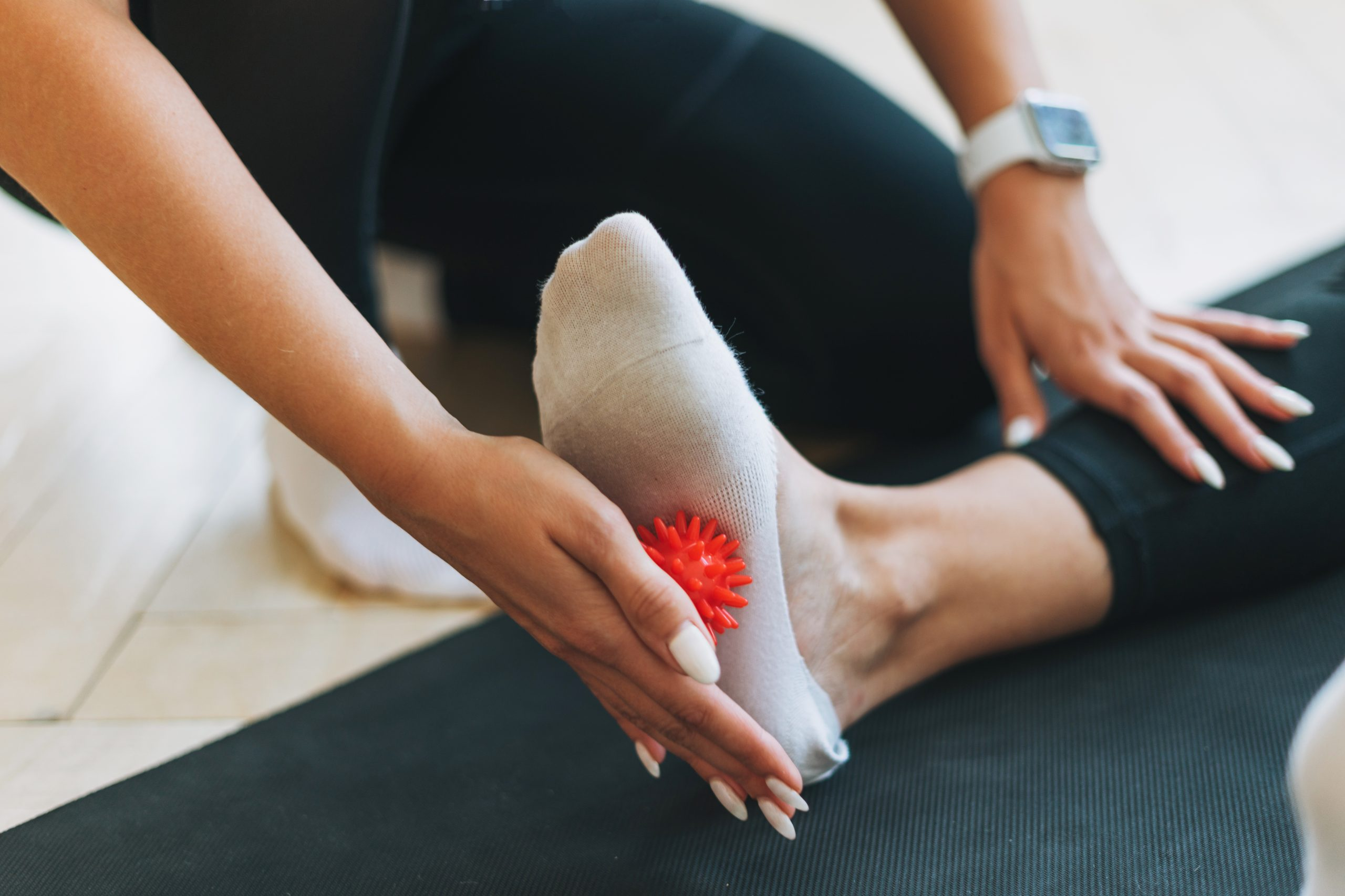 The trainer massages female feet with spiked ball, prevention of flat feet | | Featured Image for Identifying Flat Feet and Ankle Pronation | Blog